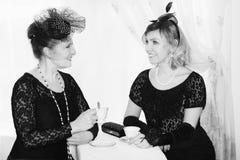 Två kvinnor som talar och ser in i de Arkivbild