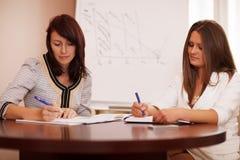 Två kvinnor som tar anmärkningar på en affärspresentation Arkivbild