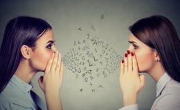 Två kvinnor som till varandra viskar en skvallerhemlighet med alfabetbokstäver i-mellan Royaltyfria Bilder