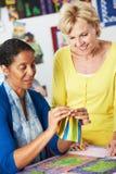 Två kvinnor som tillsammans syr täcket Royaltyfri Fotografi