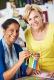 Två kvinnor som tillsammans syr täcket Arkivbild