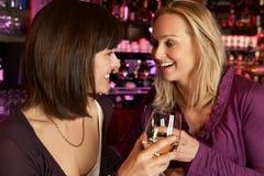 Två kvinnor som tillsammans tycker om drinken i stång Arkivbilder