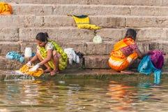 Två kvinnor som tvättar kläder i floden Ganges Royaltyfri Bild