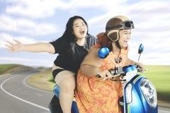 Två kvinnor som tycker om deras tur med en motorcykel Fotografering för Bildbyråer