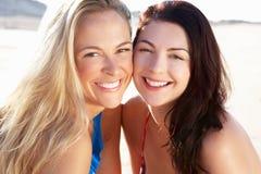 Två kvinnor som tycker om strandferie Royaltyfria Bilder