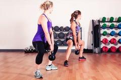 Två kvinnor som utarbetar i idrottshall Royaltyfria Bilder