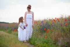Två kvinnor som utomhus rymmer händer Två kvinnor i klänningar som går nolla Royaltyfria Bilder