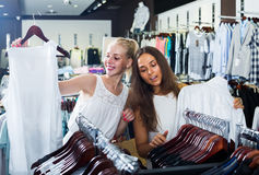 Två kvinnor som väljer den nya blusen i mode, shoppar Arkivbild