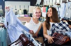 Två kvinnor som väljer den nya blusen i mode, shoppar Arkivfoto