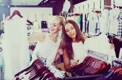 Två kvinnor som väljer den nya blusen i mode, shoppar Royaltyfria Foton