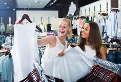 Två kvinnor som väljer den nya blusen i mode, shoppar Royaltyfri Bild