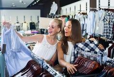 Två kvinnor som väljer den nya blusen i mode, shoppar Royaltyfri Fotografi