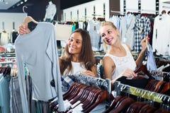 Två kvinnor som väljer den nya blusen i mode, shoppar Fotografering för Bildbyråer