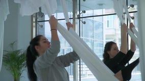 Två kvinnor svävar i hängmattan för yoga som inomhus kopplar av i studio Idrotts- flickor som öva flyg- yoga arkivfilmer