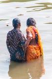 Två kvinnor tar ett rituellt bad i floden Ganges Fotografering för Bildbyråer