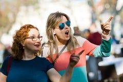 Två kvinnor - visa viktiga ställen - gest av överraskningen royaltyfri fotografi