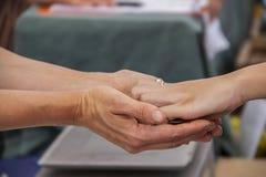 Två kvinnors händer som når från antingen sida som utbyter mynt - betala för något - den selektiva fokusen för suddig bakgrund -  arkivbilder