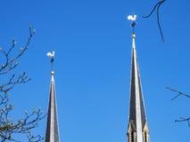 Två kyrkliga tornspiror som överträffas av vindflöjlar mot för en klar blå himmel och spirande trädfilialer för mars royaltyfri bild