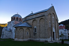 Två kyrkor inom 12 århundradeStudenica kloster på solnedgången arkivfoto