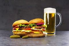 Två läckra hamburgare med ett exponeringsglas av öl på en grå bakgrund royaltyfri fotografi