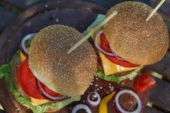 Två läckra hamburgare på träbräde Fotografering för Bildbyråer