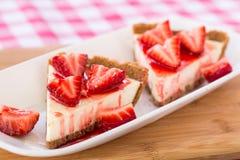 Två läckra stycken av ostkaka med jordgubbar för efterrätt Royaltyfria Bilder