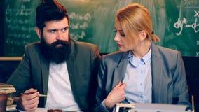 Två lärare är förlovade i en salong på bakgrunden av ett grönt bräde Lärare och deltagare lära för begrepp lager videofilmer