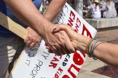 Två lärare som knäpper fast händer med protest, undertecknar bakgrund på mars för våra liv samlar in i Tulsa royaltyfri foto