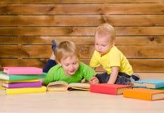 Två läseböcker för små bröder inomhus arkivbild