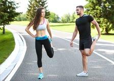 Två löpare som utomhus sprintar - Sportive folk som utbildar i a Royaltyfria Bilder