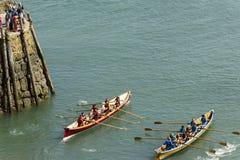 Två lag går ut skyddsmuren mot havet på Clovelly, Devon Arkivbilder