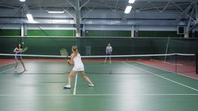Två lag som spelar tennis i dubblettlek Kvinna- och manspelareövning lager videofilmer