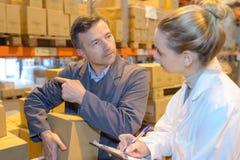 Två lagerchefer som kontrollerar inventarium i stort lager Arkivfoto