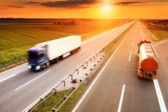 Två lastbilar i rörelsesuddighet på huvudvägen Arkivbild