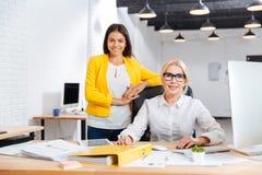Två le affärskvinnor som tillsammans i regeringsställning arbetar Arkivfoton