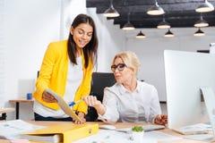 Två le affärskvinnor som tillsammans i regeringsställning arbetar på tabellen fotografering för bildbyråer