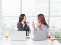 Två le asiatiska affärskvinnor som i regeringsställning arbetar med bärbara datorn royaltyfri fotografi