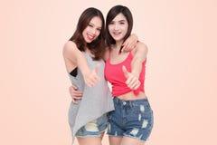 Två le asiatiska kvinnor som ger upp tummar Royaltyfri Foto