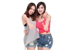 Två le asiatiska kvinnor som ger upp tummar Arkivbild
