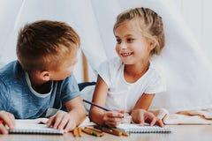 Två le barn som tillsammans hemma drar arkivfoto