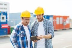 Två le byggmästare i hardhats med minnestavlaPC arkivbilder