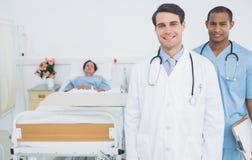 Två le doktorer med patienten i sjukhus royaltyfria bilder