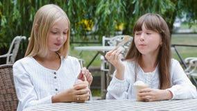 Två le flickor eller lyckliga barn med glass utomhus stock video