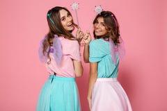 Två le flickor som kläs som feer med vingar Arkivfoton