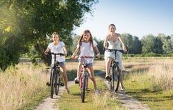 Två le flickor som rider cyklar med modern på bygdvägen Royaltyfri Bild