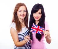 Två le flickor som rymmer den brittiska flaggan. Arkivfoto