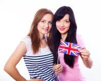 Två le flickor som rymmer den brittiska flaggan. Arkivbild
