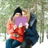 Två le flickor som sammanträde med en lila boxas räcker in arkivfoton