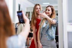 Två le flickor som tar selfie, medan shoppa i ett klädlager Fotografering för Bildbyråer