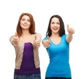 Två le flickor som visar upp tummar Fotografering för Bildbyråer